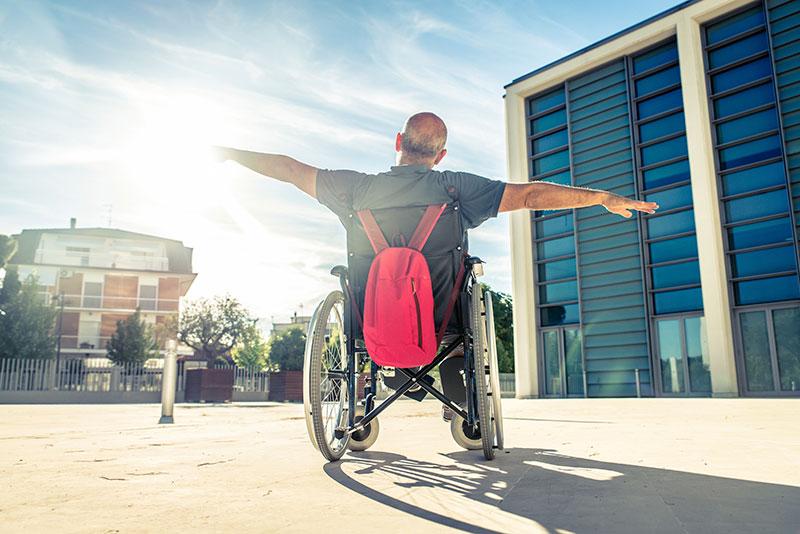 Şehir içinde binalar önünde kollarını güneşe doğru iki yana açmış tekerlekli sandalye kullanıcısı bir erkek birey. Arkadan çekim. Sandalyenin arkasına kırmızı bir çanta asılı.
