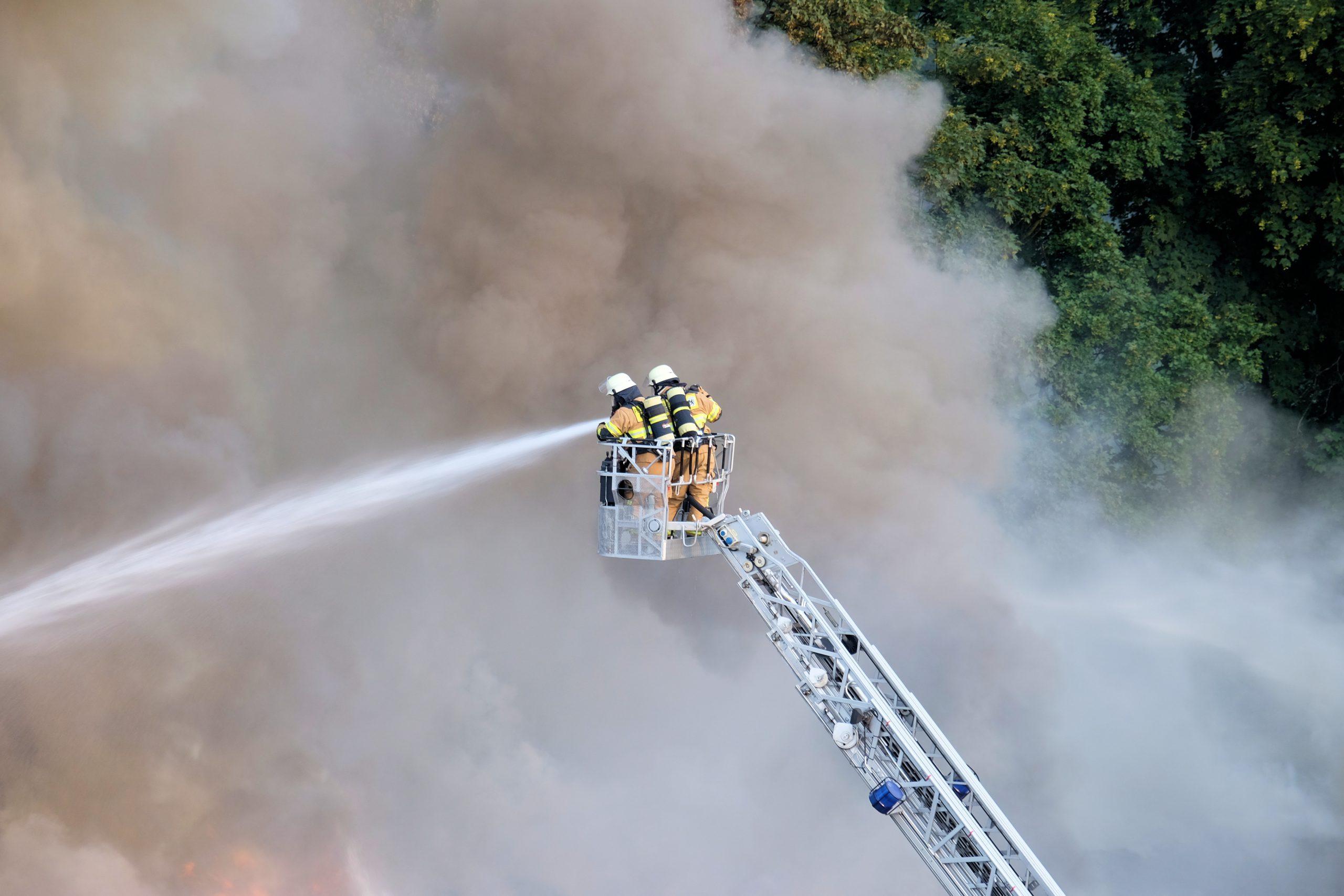 Yangından oluşan kütleli dumanlar önünde bir portatif asansörde yangına su ile müdahale eden iki itfaiye görevlisi.