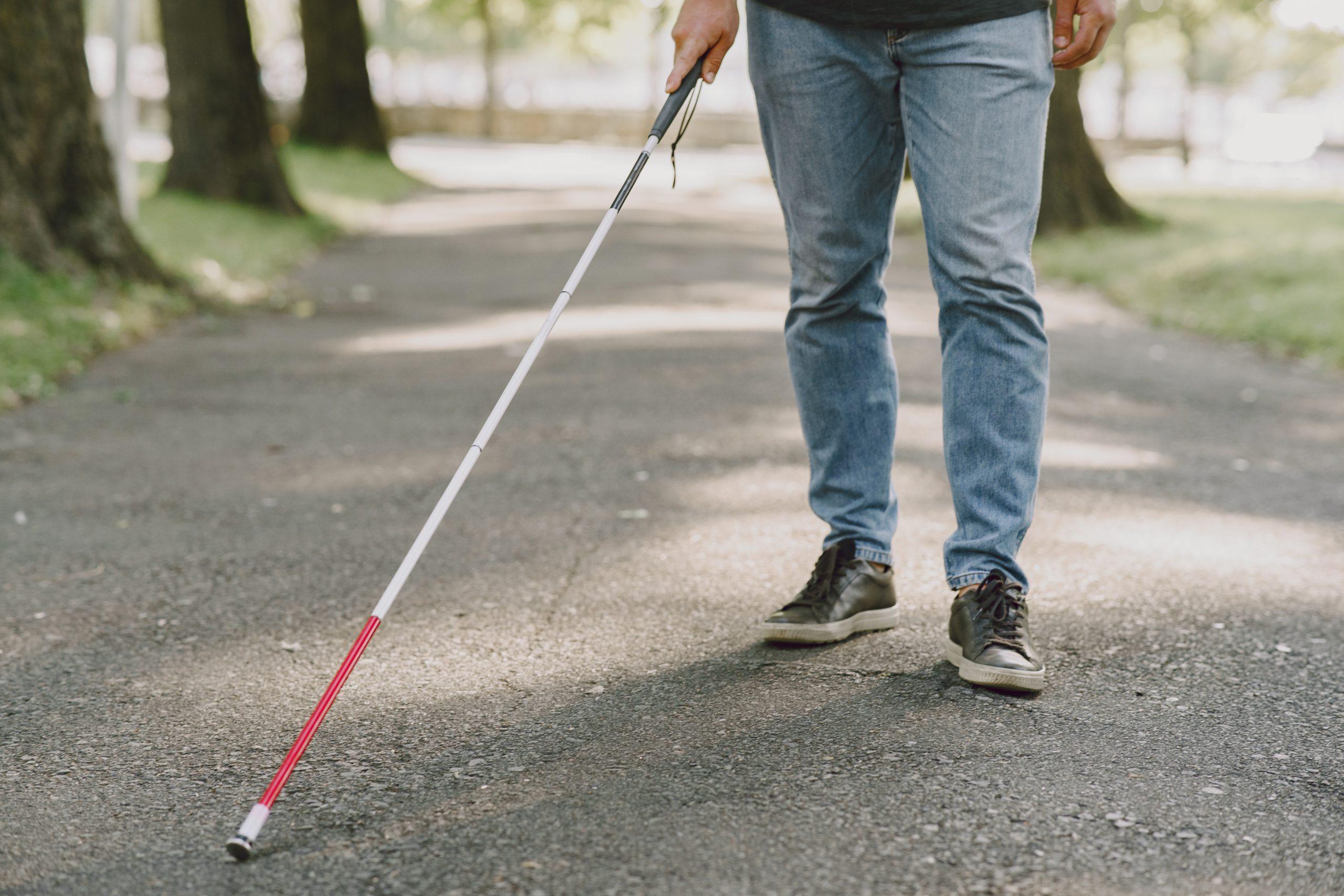 Beyaz baston kullanıcısı bir bireyin asvalt yolda yürürken çekilmiş bir fotoğrafı. Fotoğrafta bireyin yalnızca belden aşağısı görünüyor.
